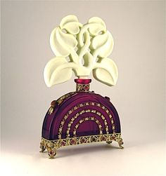 A vintage Czech glass perfume bottle in the Ingrid pattern with ruby jeweled glass and an ivory stopper, recently sold at auction.