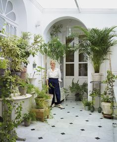 Carmen Almon in the kitchen of her Bordeaux apartment, surrounded by ficus plants and ferns.