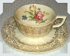 Tea Cup & Saucer Vintage mismatched Tea Cup & Saucer, Coffee Cup Saucer with Gold Ivory Pink Blue Yellow Green floral print with gold scroll / filigree boarder. There are no Makers marks on either piece but I believe the Cup is made by Sebring Pottery. It is 3 1/2 dia. and 2 1/4 tall,