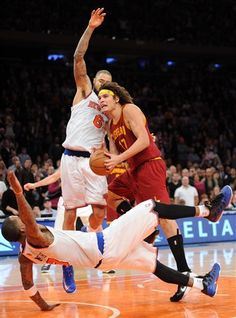 Cleveland Cavaliers' Anderson Varejao (17) is fouled as he runs into New York Knicks' J.R. Smith, bottom, and Tyson Chandler, left, during the fourth quarter of an NBA basketball game on Saturday, Dec. 15, 2012, at Madison Square Garden in New York. Varejao missed the second foul shot which would have tied the game. The Knicks defeated the Cavaliers 103-102. (AP Photo/Bill Kostroun)