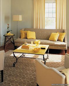 Living Room idea. Pale grey walls exposed red brick. Grey couch plus a bright colored chair and accessories in yellow/blue/green for bright color accents.