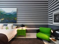 A lime green nightstand and chair add bold pops of color to this modern guest room. Navy and white striped walls set the backdrop for a colorful painting above the bed.