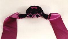 Die Kinderhaube für Mädchen besteht aus violetter Atlasseide mit aufgenähter schwarzer Tüllspitze und violetten und weißen Bändern. Die Haube stammt angeblich aus Holstein.
