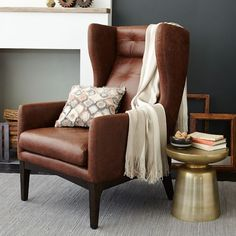 Like how the leather is softened by rug and throw pillow, and metallic table instead of dark wood