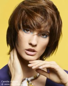 Layered hairstyle with tapered ends and bangs. Brunette.