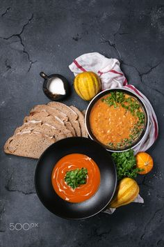 Pumpkin cream soup - Pumpkin cream soup decorated with bread, mini pumpkins, parsley, milk and napkin over dark rustic stone board. Top view