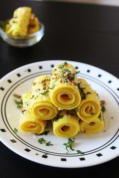 Khandvi is popular snack recipe from Gujarat (a state of India). It is made from besan or gram flour and sour yogurt. And the tempering is added on top at end which takes the dish to another level.
