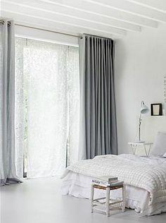 Déco chambre grise et blanc dans laquelle la seule touche de gris est apportée avec la couleur gris souris des double-rideaux. A appliquer pour le bureau
