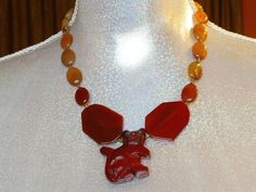 This extravagant holistic necklace is made of  carved Red Jasper pendant, free form and oval Carnelian beads withTibetan silver. Red Jasper produces a dynamic and lively energy and increases a personal powerful. It also reduces feelings of victimization and balances the third chakra. Carnelian  incr...