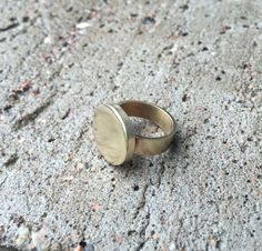 This simple handmade brass signet ring is very sturdy and comfortable to wear. Ring features 3 mm thick round brass plate that is soldered on to a wide ring band. Handmade in Finland by Katariina Wäre.