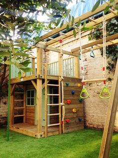 A small structure with a climbing wall, hanging swing, and a little house like…