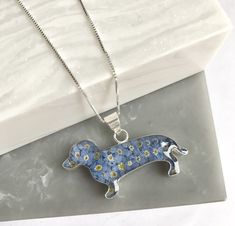 "Gorgeous necklace for a sausage dog lover! Sterling silver and real forget me not flower dachshund/sausage dog pendant on a sterling silver chain. Chain measures 16"" with a 2"" extender chain."