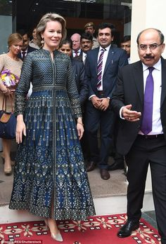 The Belgian queen consort, 44,plumped for a stunning midnight blue and gold Nadya dress b...