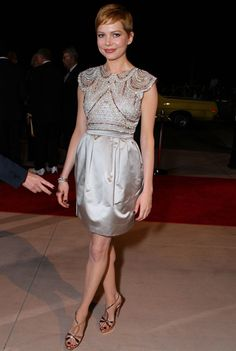 """The Look: Sparkling. The fully beaded top on this exquisite silver minidress is a perfect partner for strappy, Art Deco-esque dancing shoes.  The Girl: The actress Michelle Williams, who stars in """"My Week With Marilyn,"""" at the Palm Springs Film Festival awards gala in California.  The Details: Miu Miu dress and Prada shoes."""