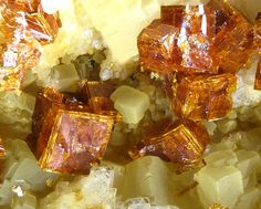 Bariopharmacosiderite,  Clara Mine, Wolfach, Black Forest, Baden-Württemberg, Germany. Sharp honeybrown bariopharmacosiderite crystals on baryte matrix