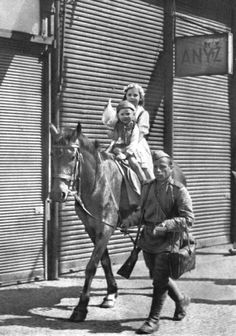 Two Czech children riding on horseback, Red Army soldier helps them. Prague, 1945, after the city was liberated by the Red Army from the Nazi invaders.