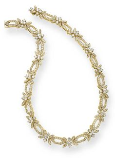 A DIAMOND NECKLACE   Designed as a series of circular-cut diamond quatrefoil motifs, extending four pavé-set diamond articulated links, alternating with pavé-set diamond stylized lozenge-shaped openwork links, mounted in 18K gold, 17 ins.