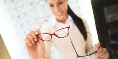Blurred image of a young smiling woman selecting eyeglasses in.