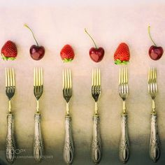 Silver forks cherries and strawberries