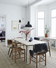 Warm furry fabrics draped over these gorgeous wooden dining chairs create cosiness in this minimalist dining space