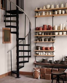 To save space, Crabtree built an iron spiral stairway (from a kit on the Internet). The shelving is bracketed with iron pipes from a hardware store. They echo the railing and allow Cain to adjust the shelf height to accommodate her work.