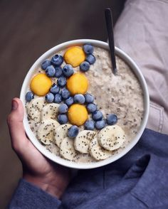 This oatmeal porridge bowl is topped with frozen blueberries, mango balls, banana slices and chia seeds. @natural.jo on Instagram