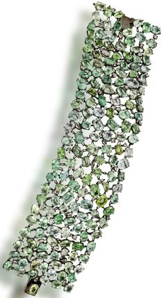 A green tourmaline and diamond bracelet,  the wide strap bracelet of openwork motif set throughout with oval and pear-shaped tourmaline in various shades of green, accentuated by intermittent rose-cut diamonds; estimated total tourmaline weight: 120.00 carats; estimated total diamond weight: 2.30 carats; mounted in eighteen karat oxidized gold; length: 7 1/2in. Via Bonhams.