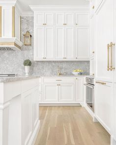 Shaker white cabinets and range with brass trim and hardware. Love the lantern next to the range