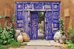 A peeling coat of deep cobalt blue paint  creates an exotic facade to the garden entry gate in a garden in Santa Fe, New Mexico