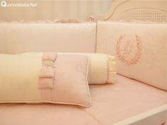 Enxoval de berço rosa com pérolas e lacinhos no estilo princesa. A proteção lateral contém as iniciais do bebê.