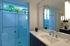 A white tile shower with a clerestory window and sliding glass doors combines with light walls and crisp white countertops for a bright, breezy atmosphere in this contemporary master bathroom.
