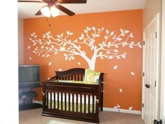 Tree decal is too cute. The orange should be downplayed a bit with more furniture or on a smaller wall.