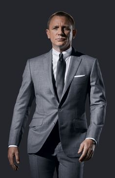 Daniel Craig in grey sharkskin TOM FORD O'Connor suit. Promo still for SKYFALL. White French cuff tab collar shirt, silver chain link patterned silk tie, and white linen pocket square all by TF.