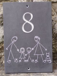 Slate house number plate with number sandblasted, family hand drawn and hand engraved. All painted silver, on rectangular slate plaque.