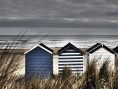 Beach Huts and Sand Dunes Suffolk coast of England. Painted beach huts amongst the dunes looking out to the ocean.    The photograph is a traditional C