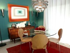 David gives this small dining area a funky new vibe with artwork he painted himself, a modern aluminum chandelier and a moody, blue-green wall color. The homeowners' existing dining set is right at home in the new space.