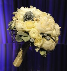 Winter themed bridal bouquet with white pine cones and white roses. #wedding #flowers #bouquet #winter #pine #cones