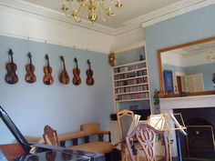 I like how they use a picture rail to hang the violins on the wall. Interesting idea for a music room.