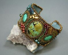 Bead-embroidered cuff bracelet by Nancy Arditi. Beads, pearls and cabochons on metal form with fabric or ultrasuede backing.