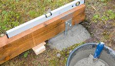 Legen Sie die Bodenbalken auf Futterhölzern so aus, dass die montierten Pfostenhalter mittig in die Fundamentlöcher ragen und richten Sie sie waagerecht aus.