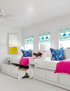 White built-in nightstands topped with white glass globe lamps flank white built-in trundle beds dressed in pink and white bedding accented with blue paisley pillows.