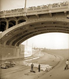 Two policemen standing over body of man who jumped from First Street Bridge in Los Angeles, as a crowd watches from the bridge (ca, 1948).  This shot appears in the main titles of the TNT television series SOUTHLAND.