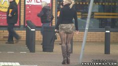 Woman in ultra short leopard print skirt and fishnets flashing her bum cheeks in public.