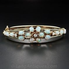 A glowing display of sixteen pretty pastel-colored opals are arrayed across this 14 karat yellow gold hinged bangle bracelet, culminating in...