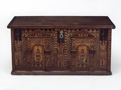 The name Nonsuch or Nonesuch is given to early inlaid chests of this type in which the design of the inlay is architectural in character and represents a quaint building with castellations, high-pitched roofs, cupolas and steeples set with vanes, and flying flags. V