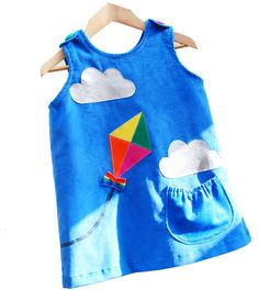 Wild Things Kite Dress Wild Things Dresses is a fun new label for little girls which offers simple, versatile dresses with a funky contemporary twist. Brighten up any day with this beautiful blue cord applique pinafore! Fluffy clouds with pretty multi-coloured kite and rainbow bow. The kite sweeps around the simple A line shape giving a fantastic 360 degree view… Button fastening at shoulders. 2/3 lined in self fabric. Cord is a good weight for any season.