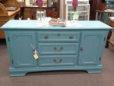SOLD - This all wood cabinet has 3 Center drawers and two cabinet doors for additional storage. It has been painted turquoise, lightly distressed and finished with a dark wax. It measures 59 inches across the front, 17 inches deep and it stands 31 inches tall. It can be seen in Booth D2 at Main Street Antique Mall 7260 East Main St ( E of Power Rd ) Mesa 85207  480 9241122open 7 days 10 till 530 Cash or charge 30 day layaway also available