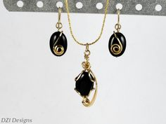 "14k (14/20) rolled gold and black onyx earrings and necklace set. The earrings consist of a 14x10mm banded black onyx gemstone with sculpted 14k rolled gold that swirls on the face of the gem. The necklace consist of a 14x10mm banded black onyx gemstone that is wire sculpted with artistic swoops and curls that showcase the beautiful black onyx gemstone. This one of a kind pendant sets on a 18"" 14k gold plated necklace. Approx size of earrings:  1"" in total length by 3/8"" in width"