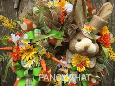 Adorable sisal bunny with a top hat against polyjute burlap ruffles surrounded by tons of fern, florals in orange, white, yellow and embellished with carrots. Gerbera daisies, wild flowers, daffodils, grasses and fern give that feel of a spring garden. Matching wired edge ribbon in plaid, polka dot and solid finished off with an XL bow. Tiny butterflies flutter about in the garden of florals and a tiny bird tucked in. This wreath will make a statement for your Easter front door decor, over a…