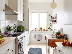 a white kitchen with wooden countertops and table. Some splashes of colour and plenty of greens keep it cozy looking